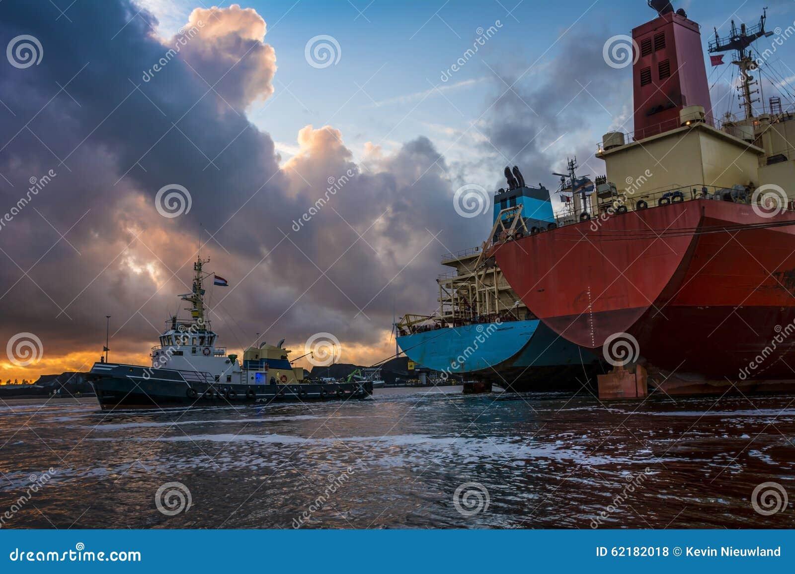 De koopvaardijschepen zijn bezig met meertrosverrichtingen tijdens zonsondergang in haven