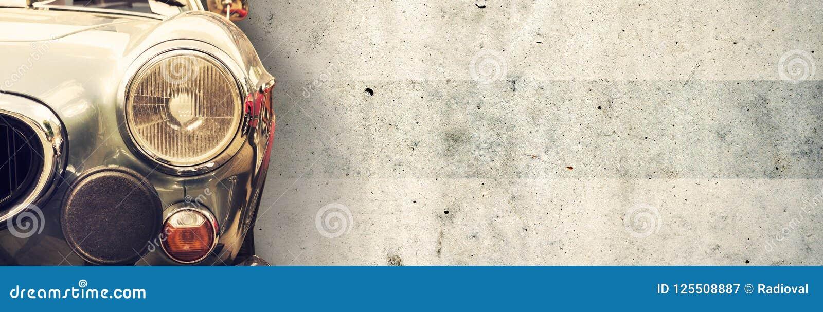 De koplamp van de oude mooie auto op de achtergrond van een concrete muur De ruimte van het exemplaar De reparatie van conceptenb