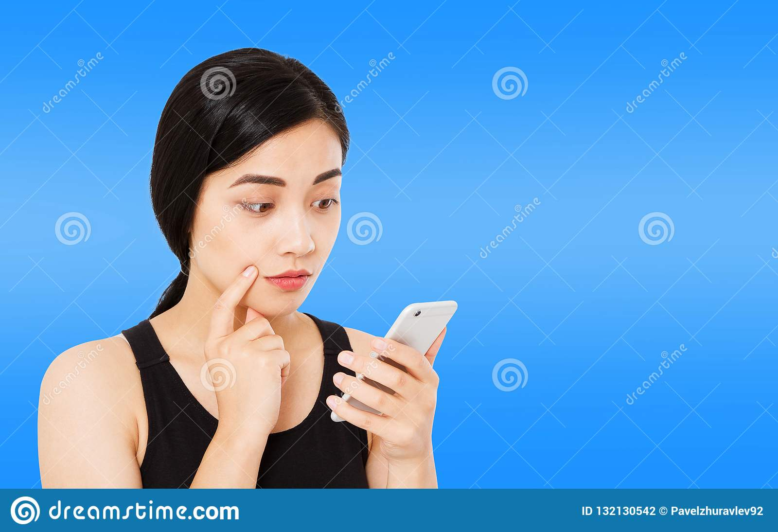 De Koreaanse, Aziatische die vrouw leest nieuws zorgvuldig op donkerblauwe achtergrond, de telefoon van meisjeshol, exemplaarruim
