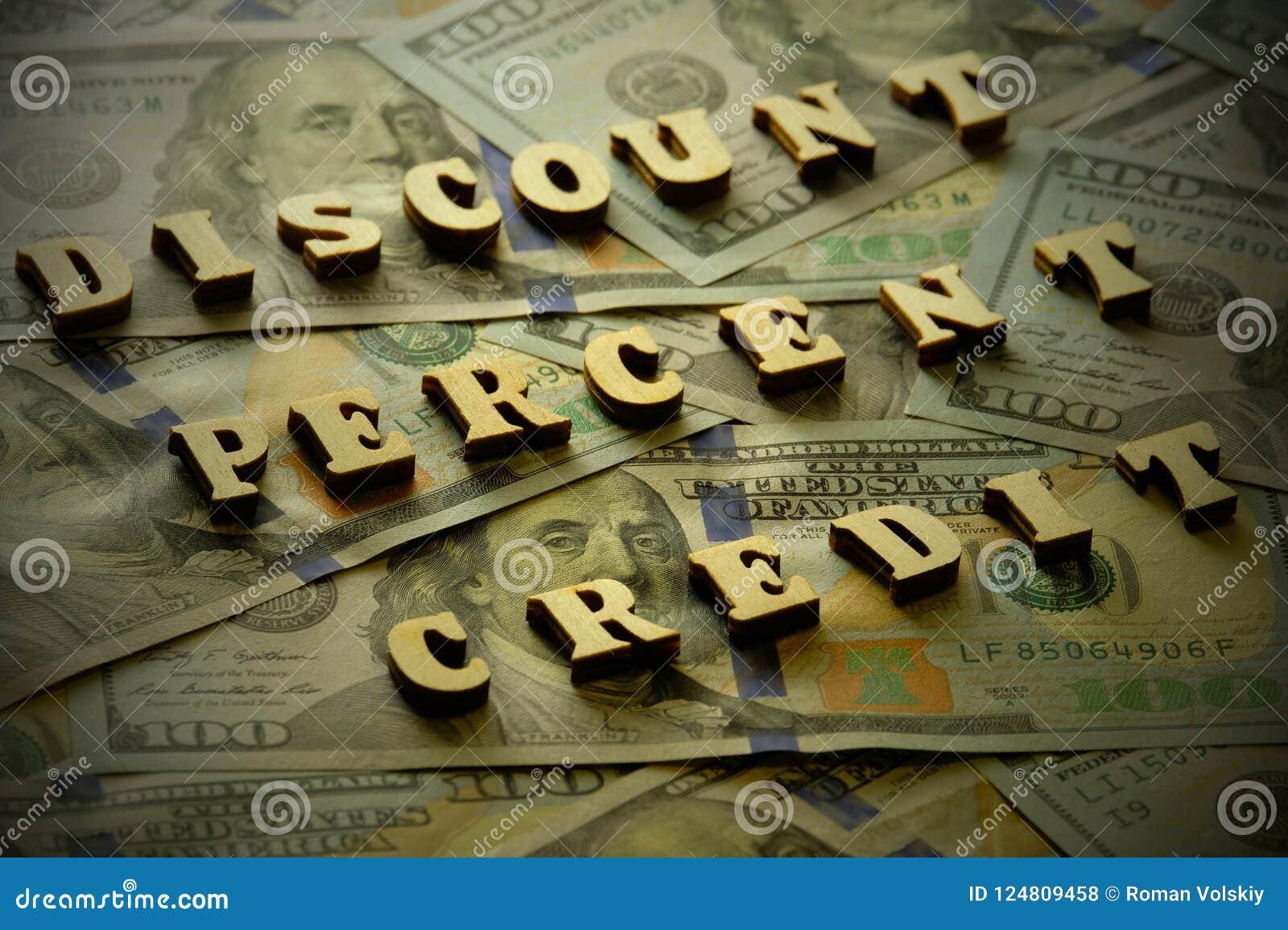 De KORTING, PERCENTEN, KREDIET wordt opgemaakt van houten brieven op de achtergrond van honderd-dollar rekeningen toning vignetti