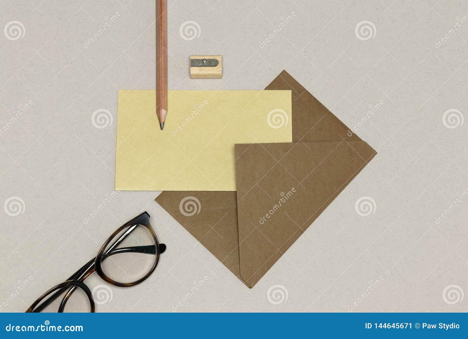 De kraftpapier-envelop, het houten potlood & de slijper, bril op de witte textuur