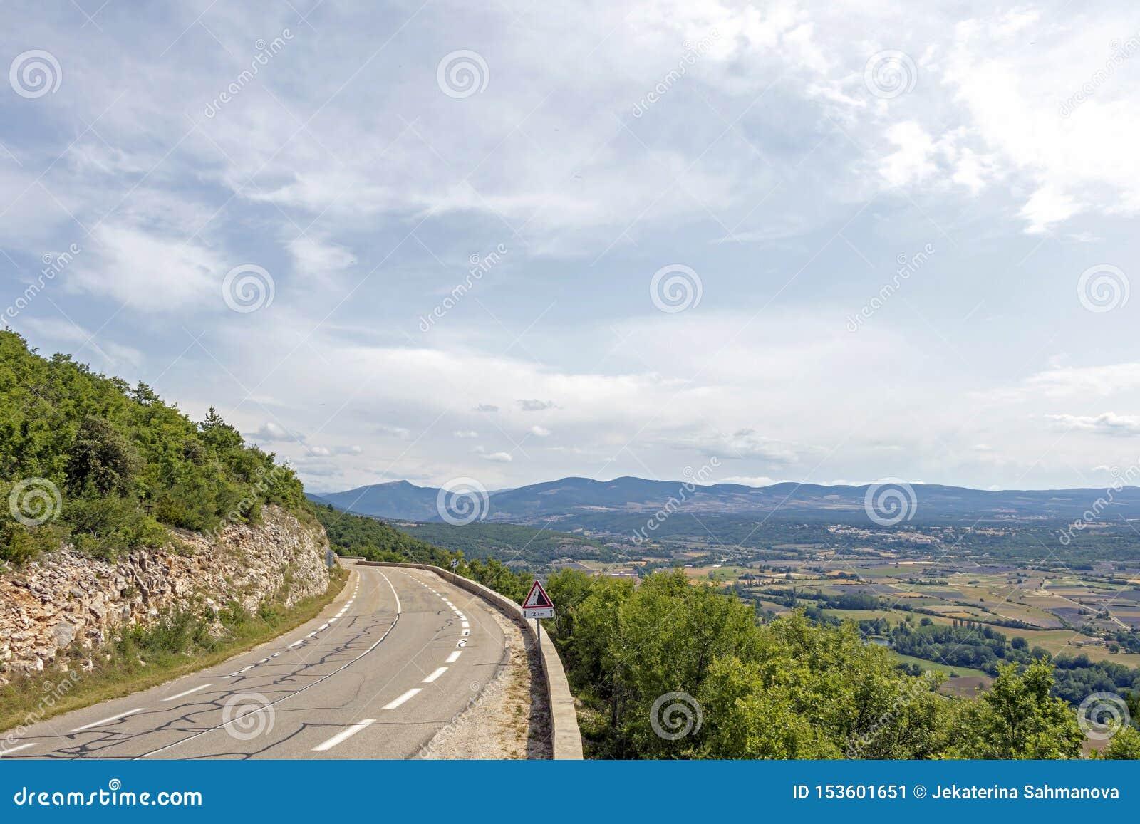 De kromme van de bergweg boven de bos en landbouwgebieden in Frans platteland