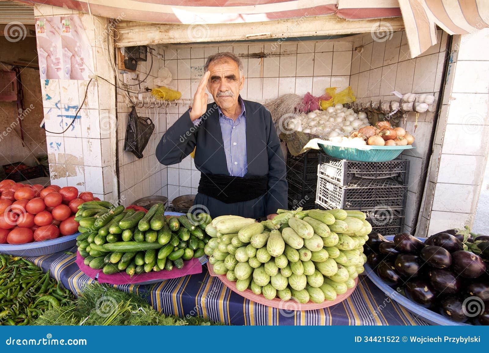 De kruidenier begroet zijn cliënt die zich achter zijn groenten in kleine winkel in Bazaar bevinden. Irak, Midden-Oosten.