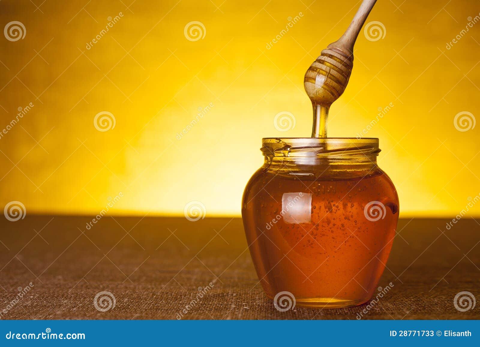 De kruik van de honing met dipper