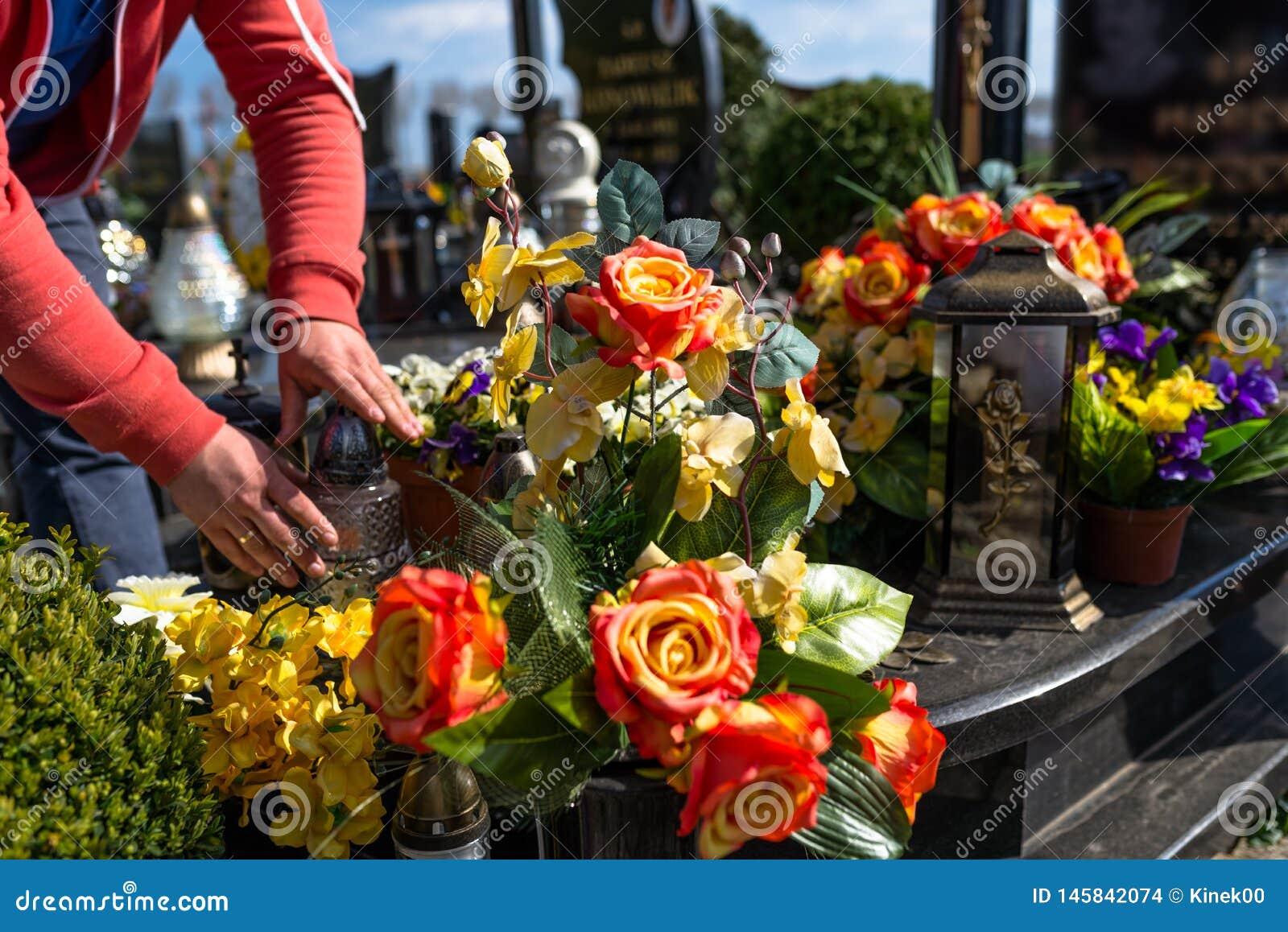 De kunstbloemen en de kandelaars liggen op de grafsteen in de begraafplaats, zichtbare handen van een mens