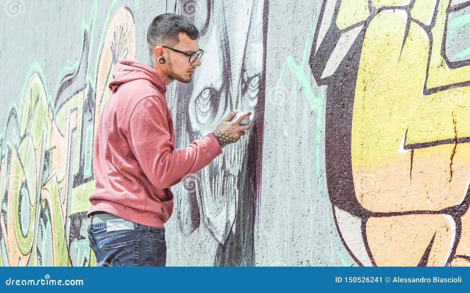 De kunstenaar die van de straatgraffiti met een kleurenaërosol een donkere graffiti van de monsterschedel op de muur in de stad s