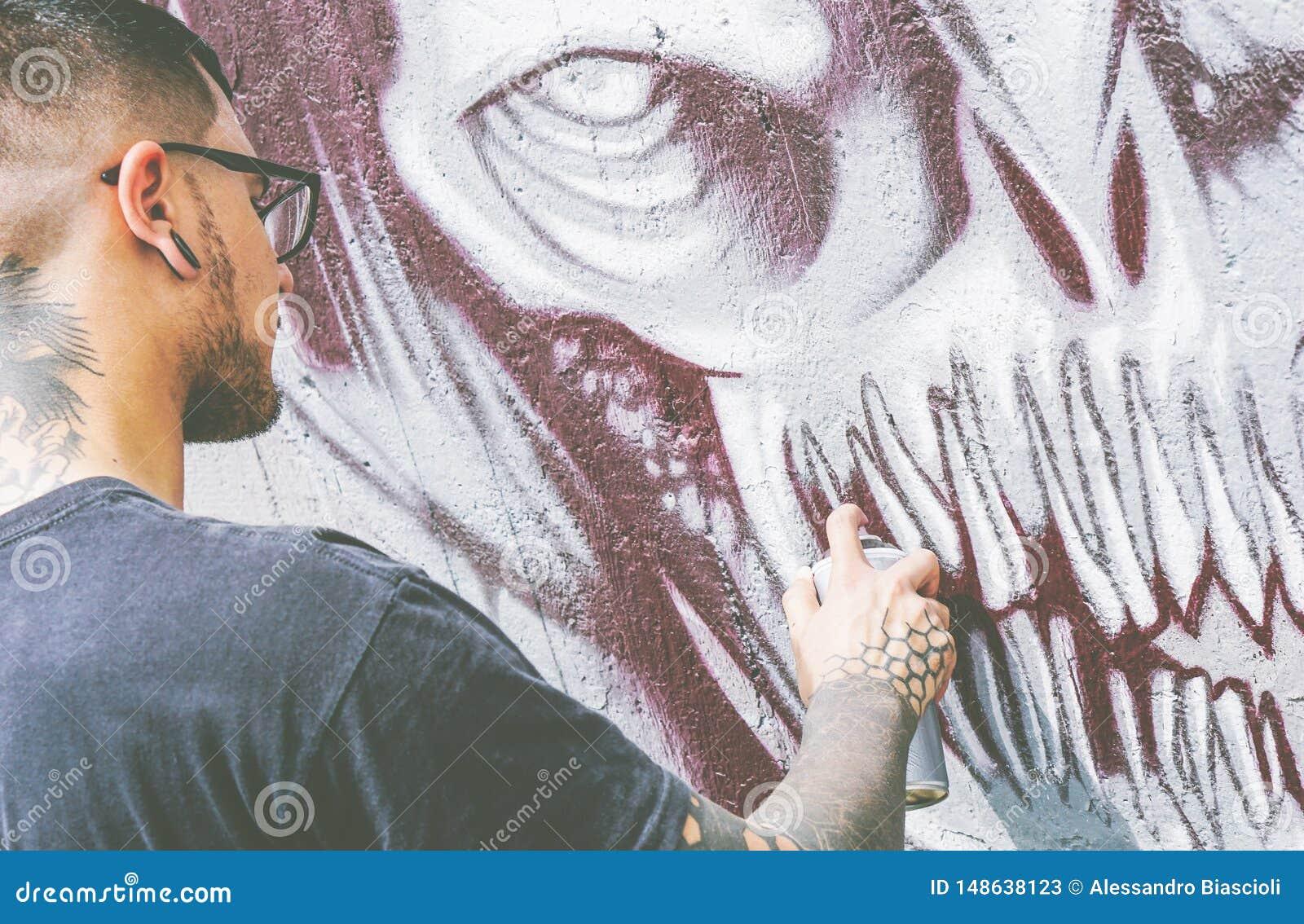De kunstenaar van de straatgraffiti het schilderen met een kleur bespuit een donkere graffiti van de monsterschedel op de Stedeli