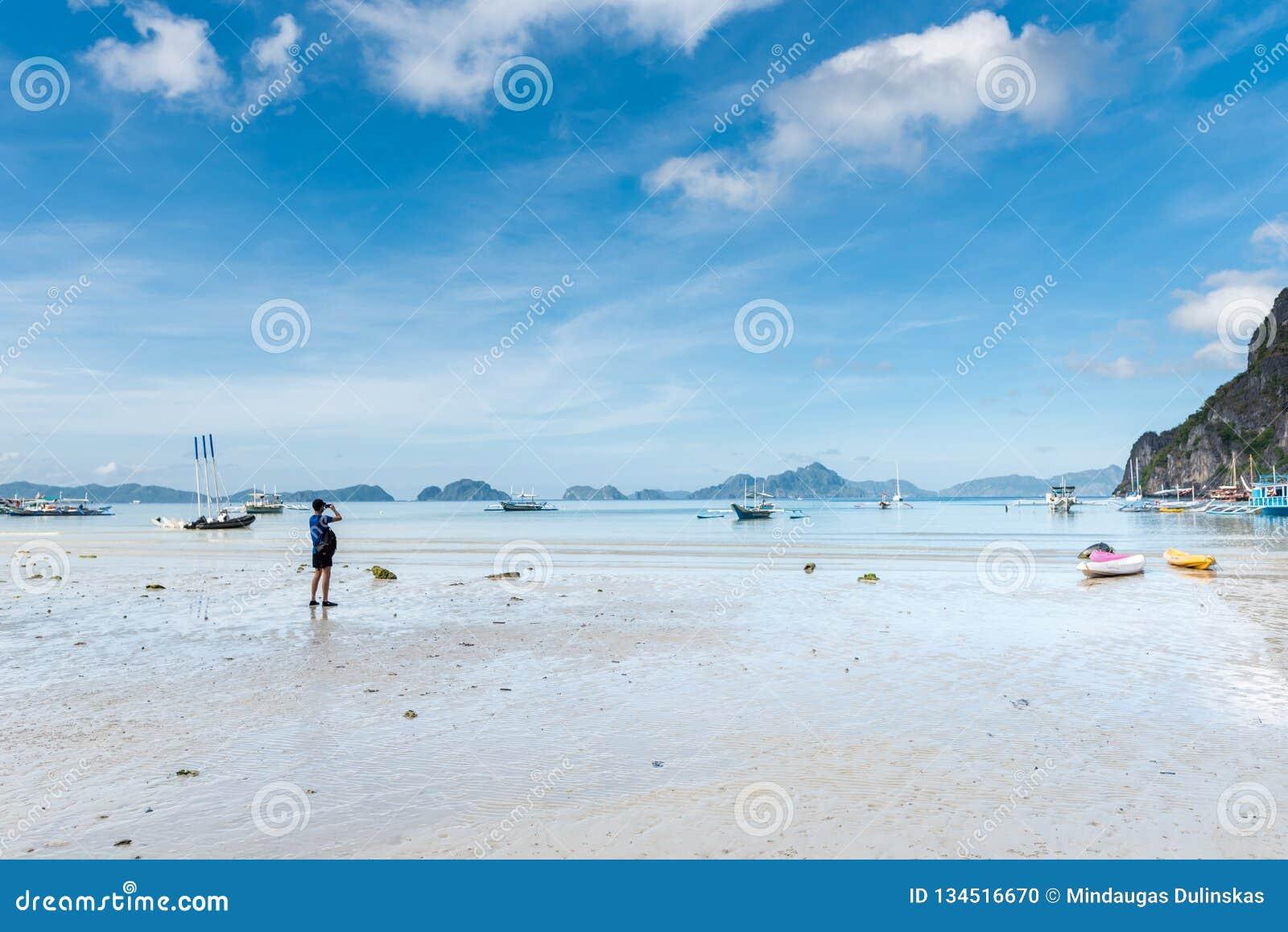 De Kust van Gr Nido in Palawan Eb en Berg met Boten op Achtergrond