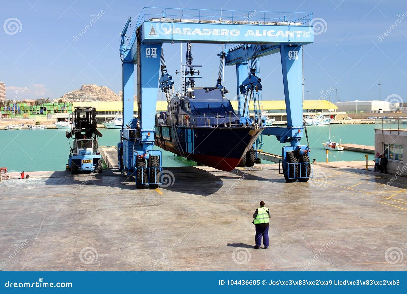 De kustwacht van de Spaanse Douane over een travelift vóór gaat naar het water