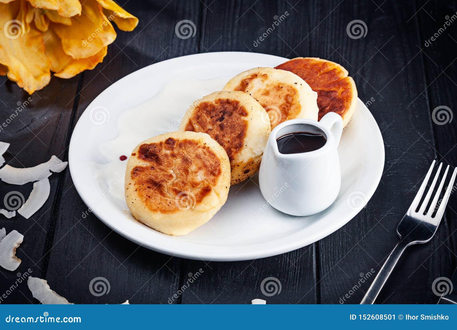 De kwarkpannekoeken dienden op witte plaat met hete chocolade op donkere houten achtergrond Traditioneel eigengemaakt Oekra?ens v