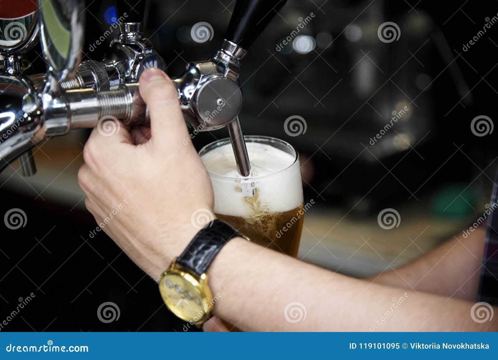 De la bière est versée du robinet dans un verre de bière de mousse