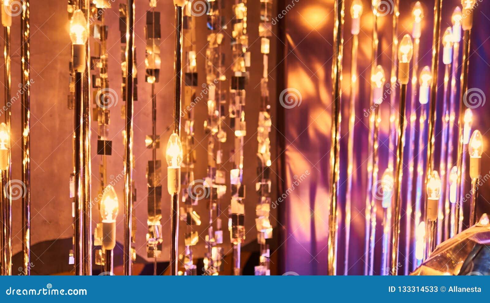 De la Noche Vieja el fondo borroso de la celebración festiva con los vidrios de champán Fuegos artificiales y bokeh del oro del v