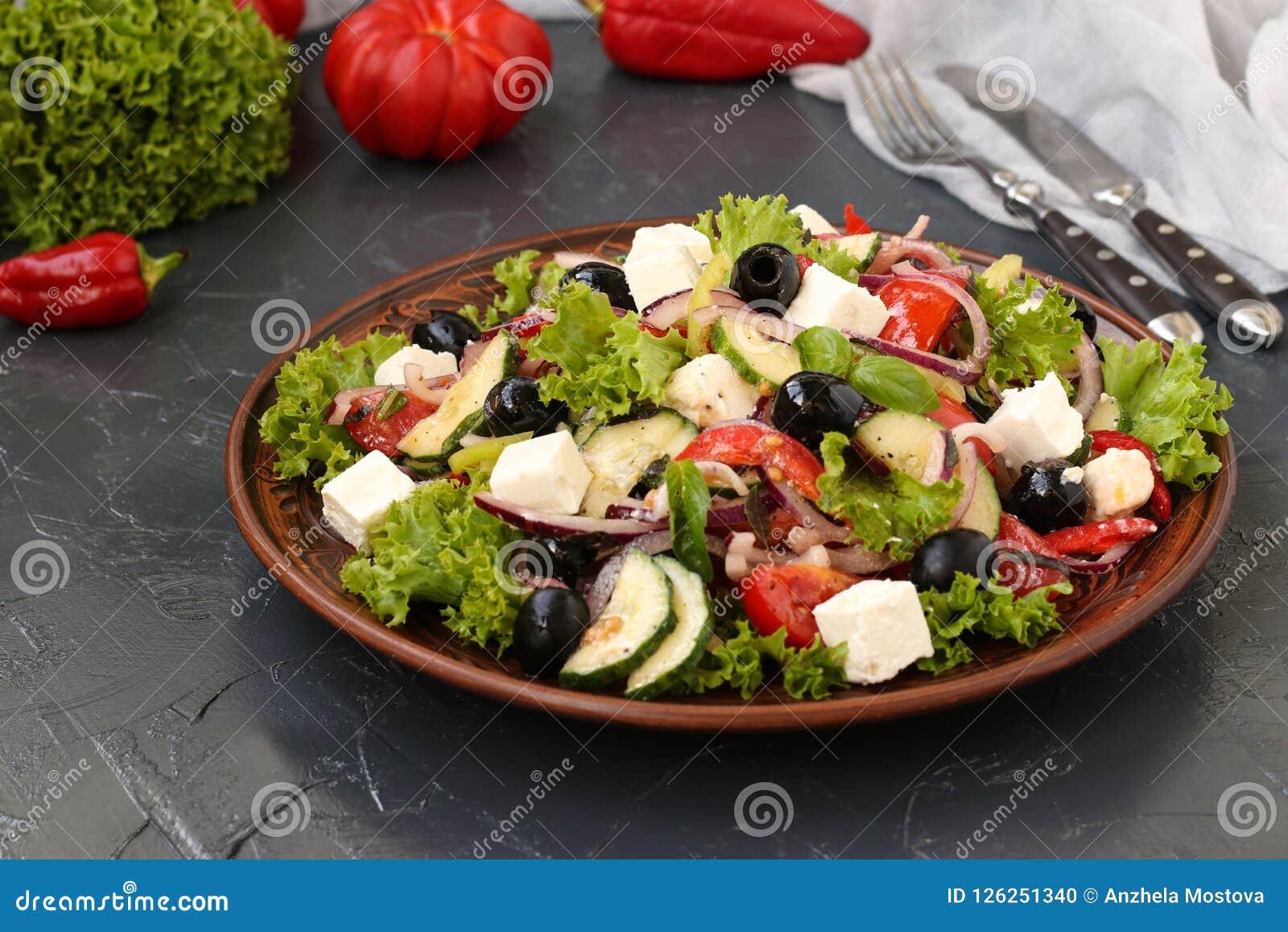De la salade grecque est située sur un plat sur un fond foncé