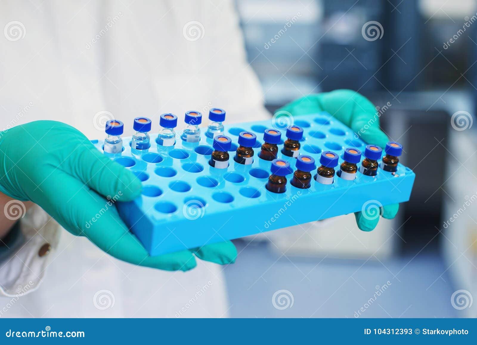 De laboratoriumwetenschapper houdt een plastic doos met steekproeven van transparante vloeistof in de flesjes