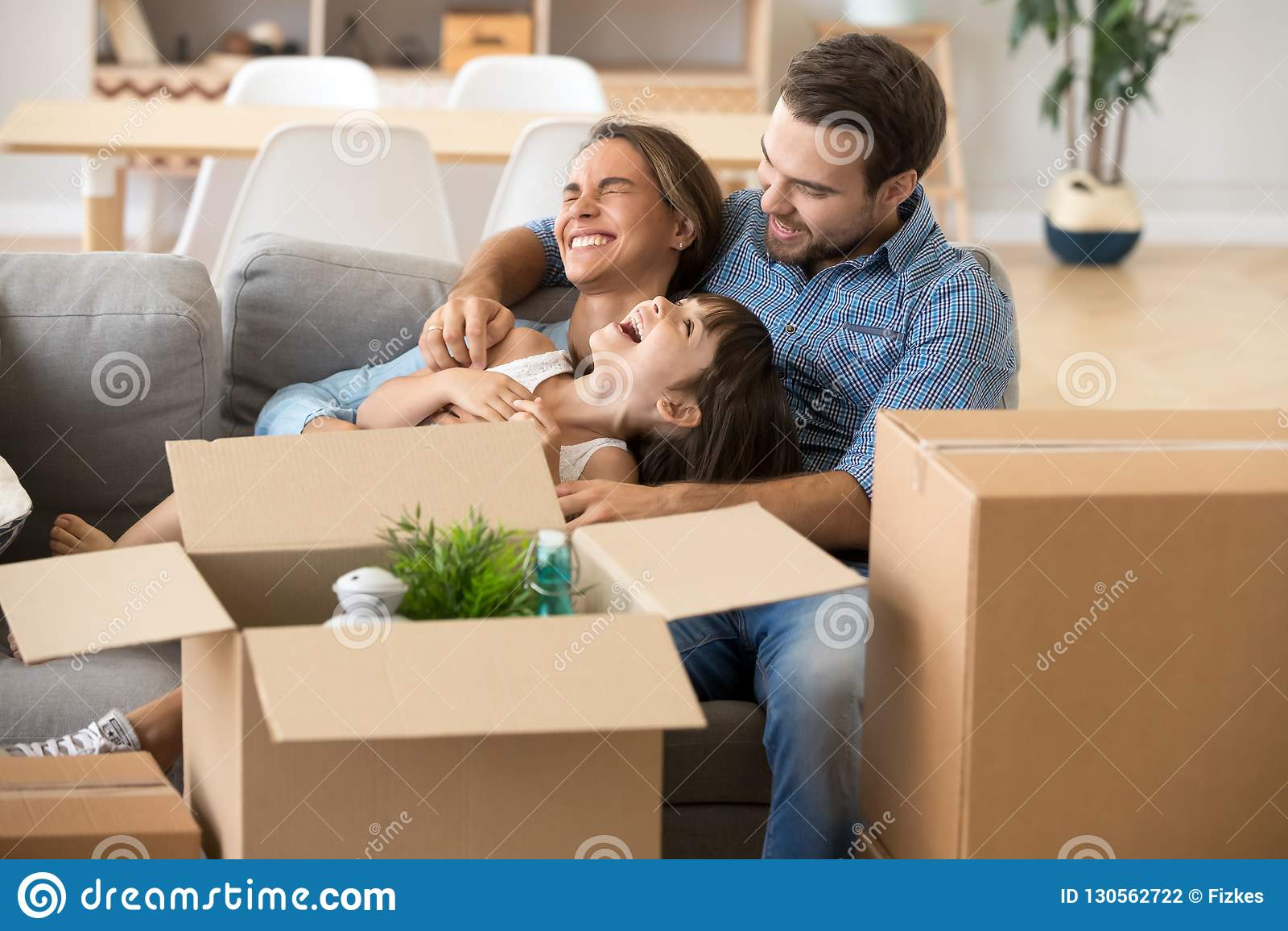 De lachende familie brengt tijd door die pret hebben bij nieuw huis
