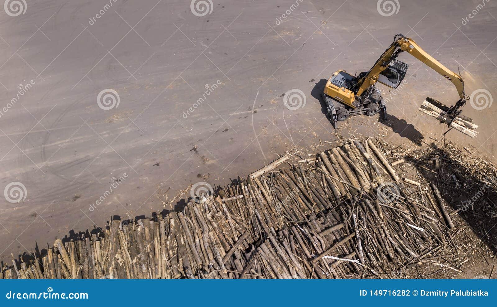 De lader laadt de houten stralen in de vrachtwagen