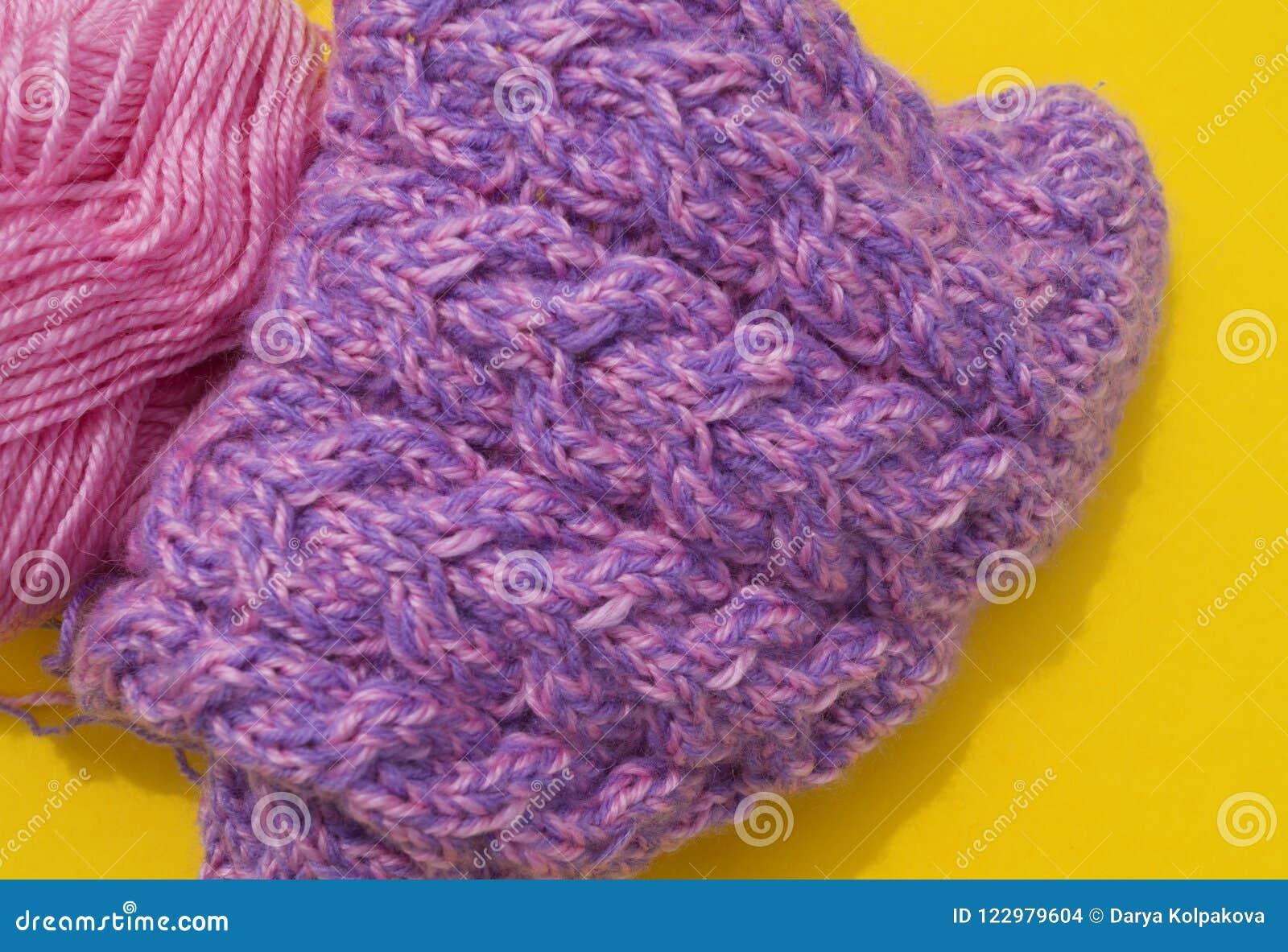 De lagen van wolroze en purple liggen naast een afgekoppeld GLB Gele achtergrond
