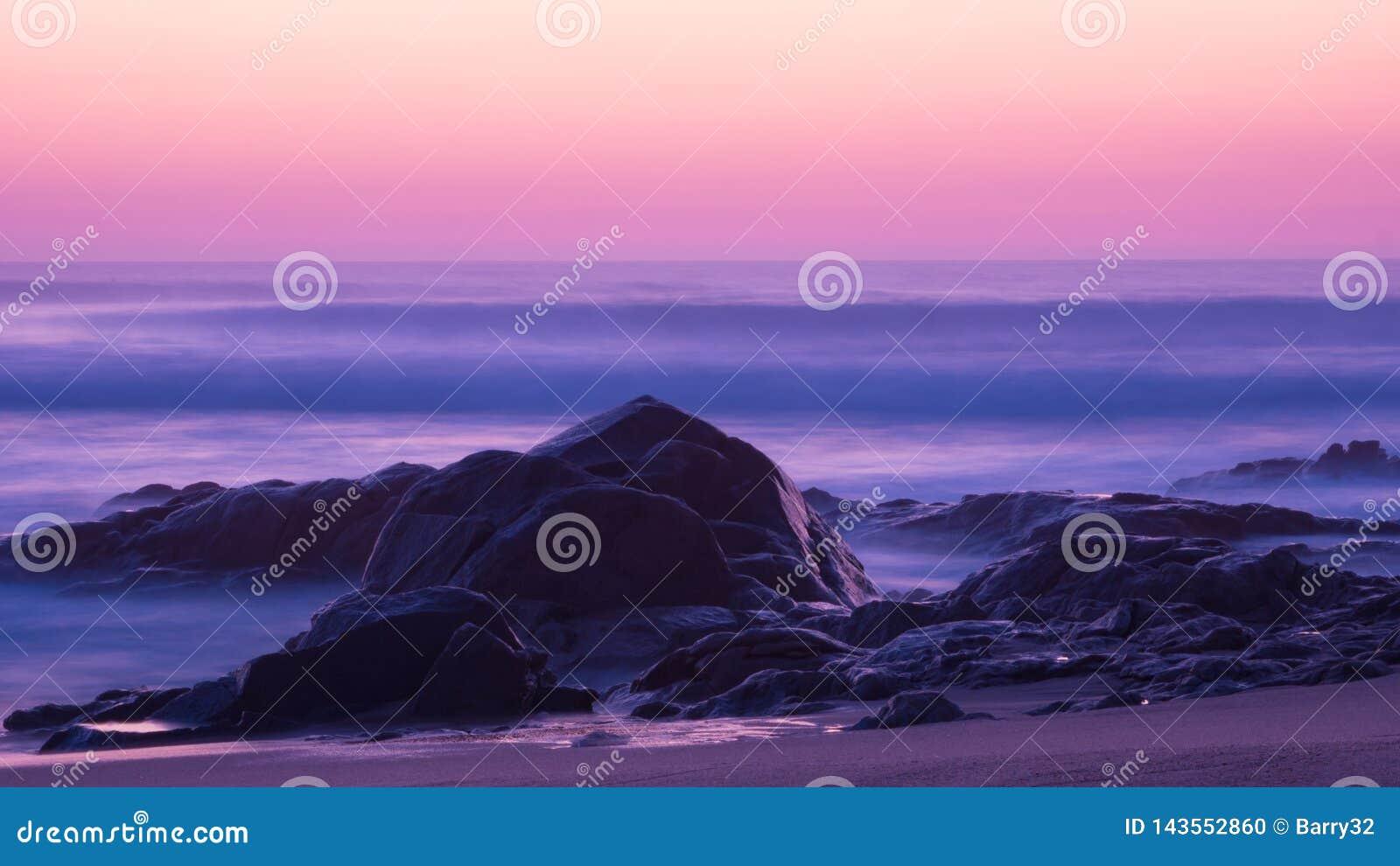 De lange blootstelling schoot bij schemer over oceaan met erachter rotsen in voorgrond en melkachtige golven