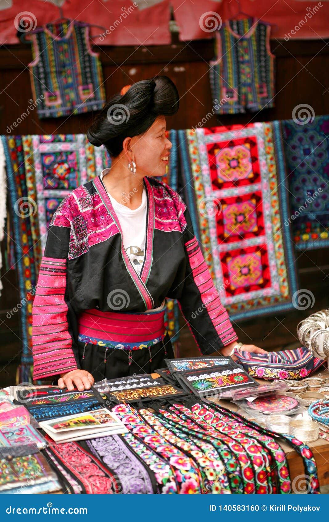 De langharige vrouw van de Yao-mensen verkoopt herinneringen aan toeristen