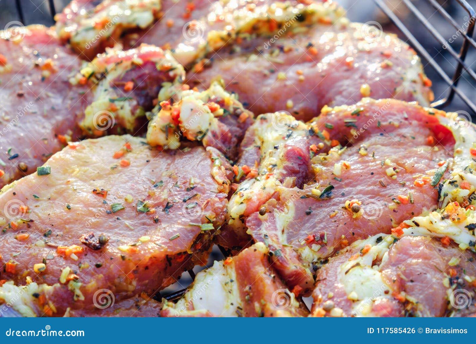 De lapjes vlees van het rundvleesvlees Verse ruwe varkensvleeshals voor lapje vlees met kruidkruiden op een barbecuegrill