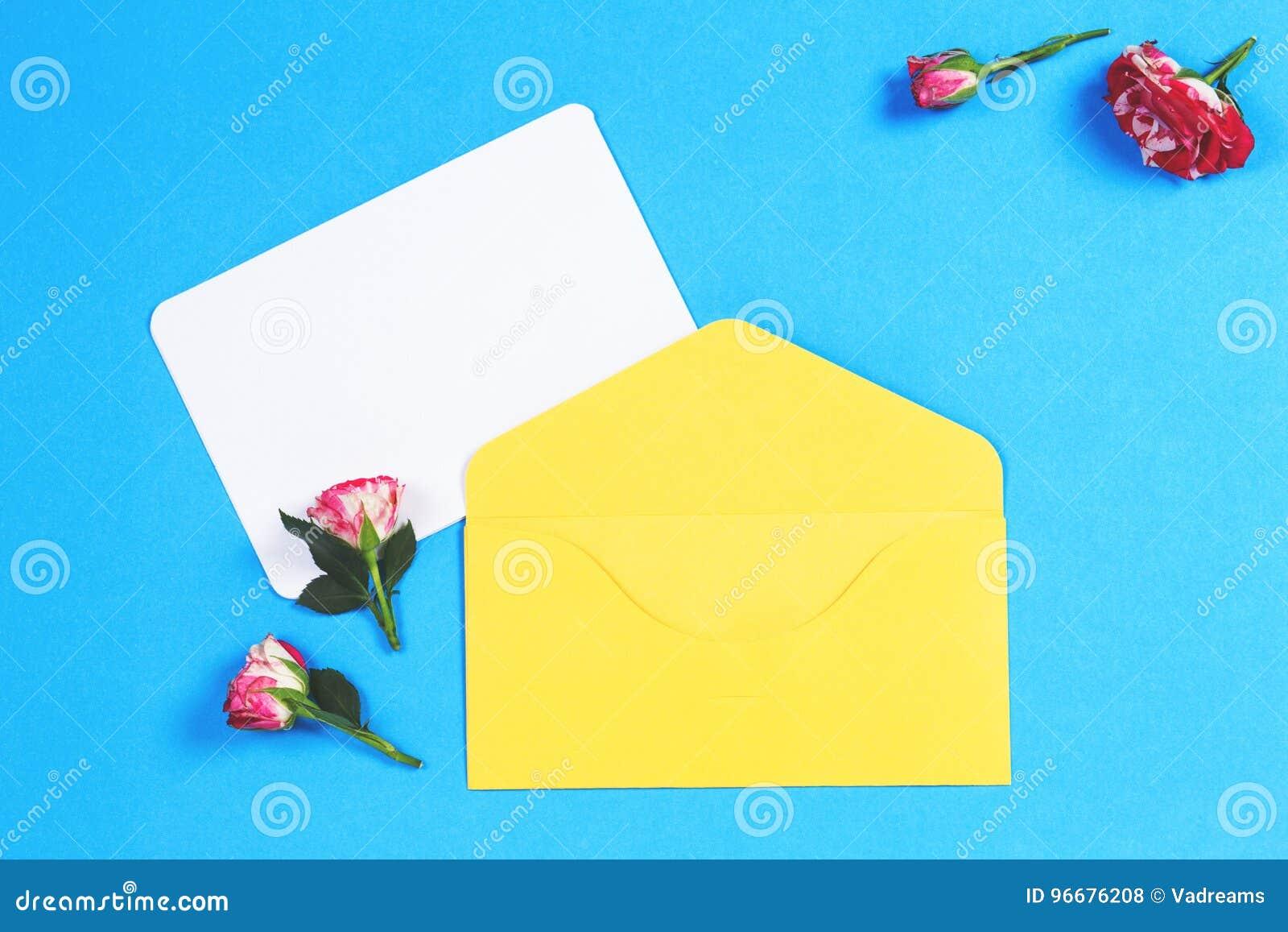 De lege groetkaart met gele envelop en roze nam bloemen op blauwe achtergrond toe