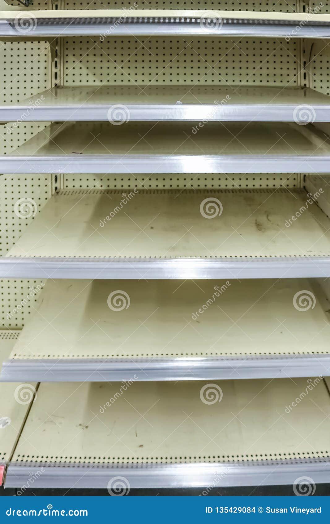 De lege planken van het opslagmetaal na seizoengebonden goederen worden uitgever*kopt wachtend op nieuwe koopwaar