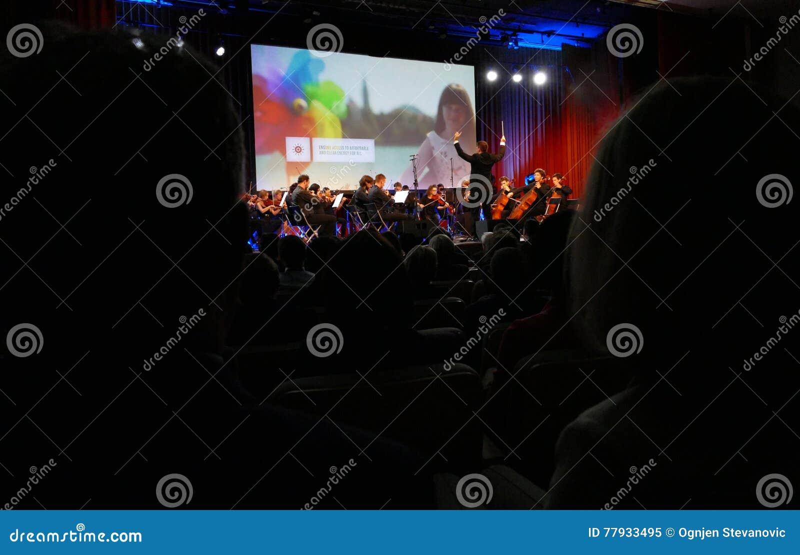 De leider die symfonieorkest met uitvoerders op achtergrond leiden tijdens de openingsceremonie van Zaken tapte Strategisch Forum