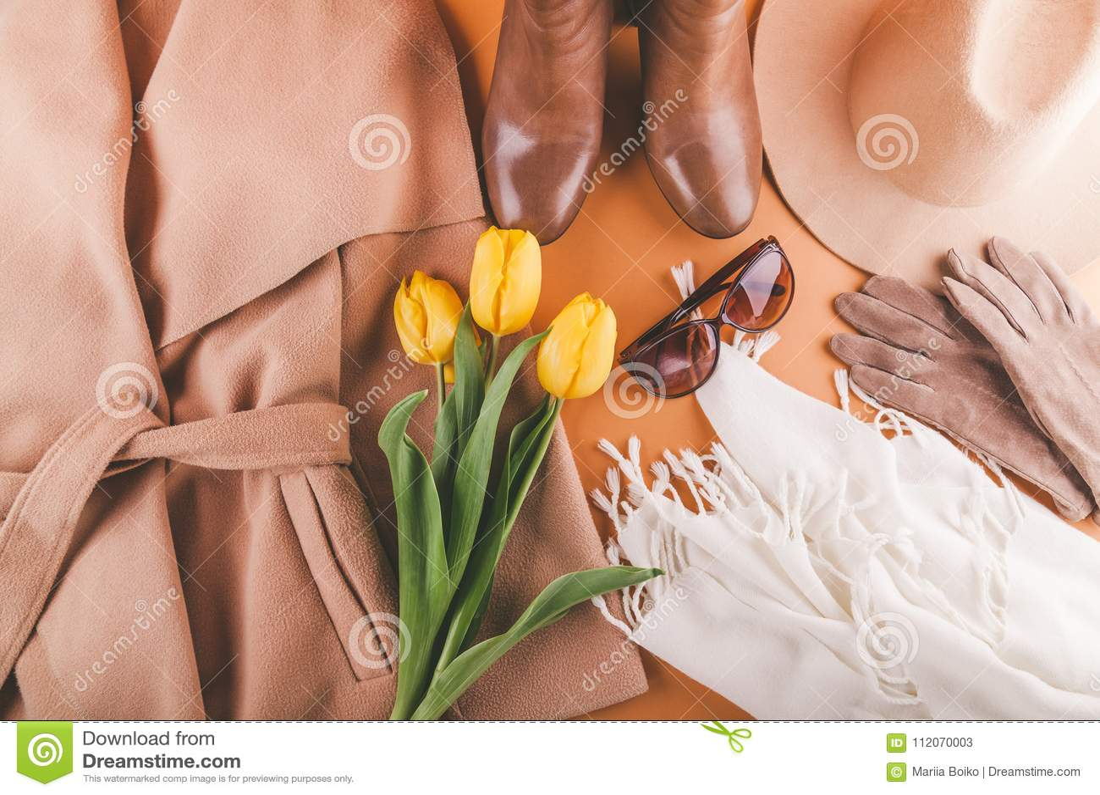 De lente vrouwelijke uitrusting met gele tulpen Reeks kleren, schoenen en toebehoren op oranje achtergrond