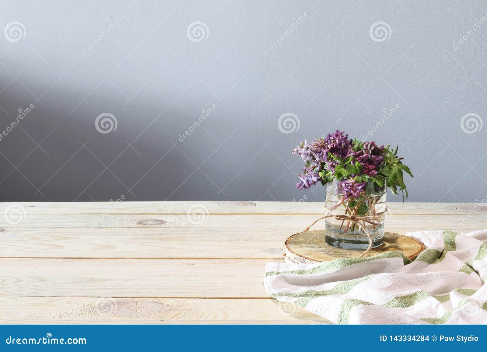 De lentebloemen en witte handdoek op het houten bureau