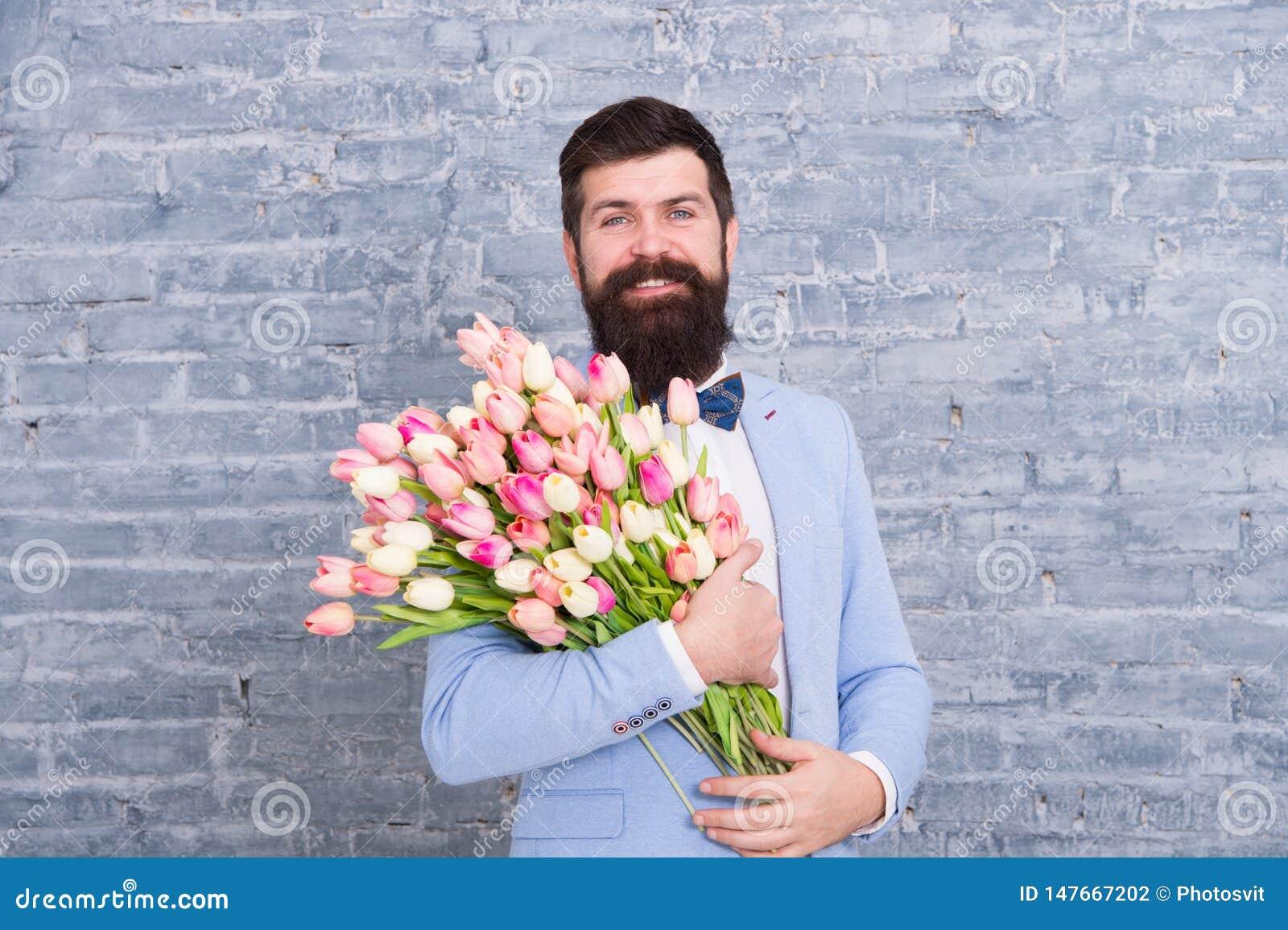 De lentestijl De dag van vrouwen is op 8 maart De lentegift Gebaarde mens hipster met bloemen De datum van de liefde Internationa