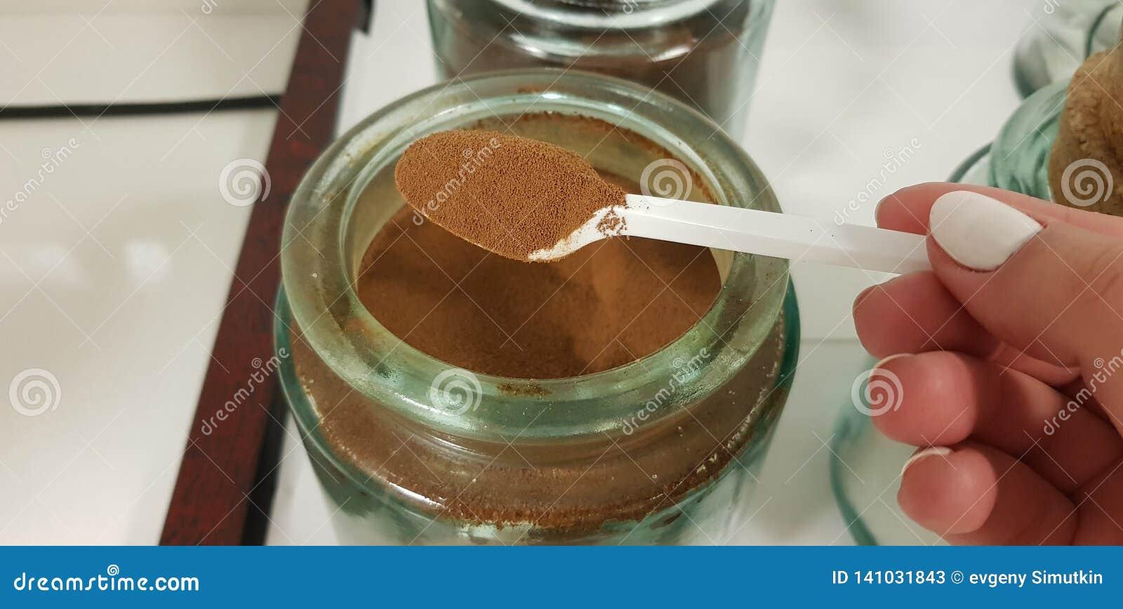 De lepel met onmiddellijke koffiepoeder in vrouwelijke vingers over groot glas kan met koffie