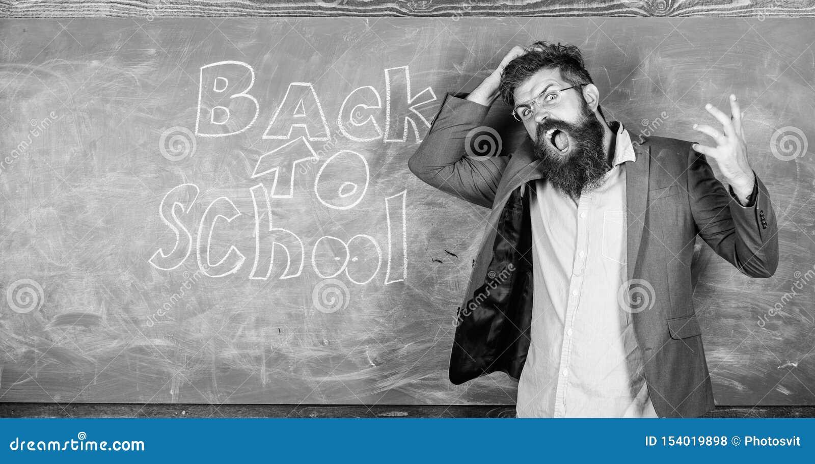 De leraar of de opvoeder bevinden zich dichtbij bord met inschrijving terug naar school Leraars ongelukkig hysterically schreeuwe