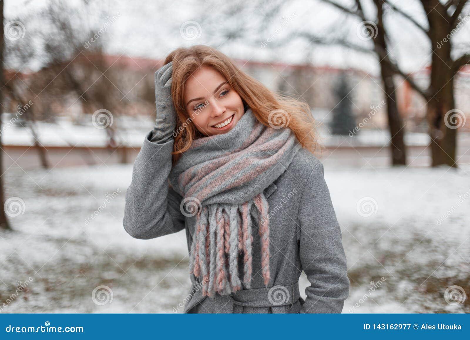 De leuke aantrekkelijke vrij jonge vrouw in grijze handschoenen in een in grijze laag met een uitstekende gebreide sjaal bevindt