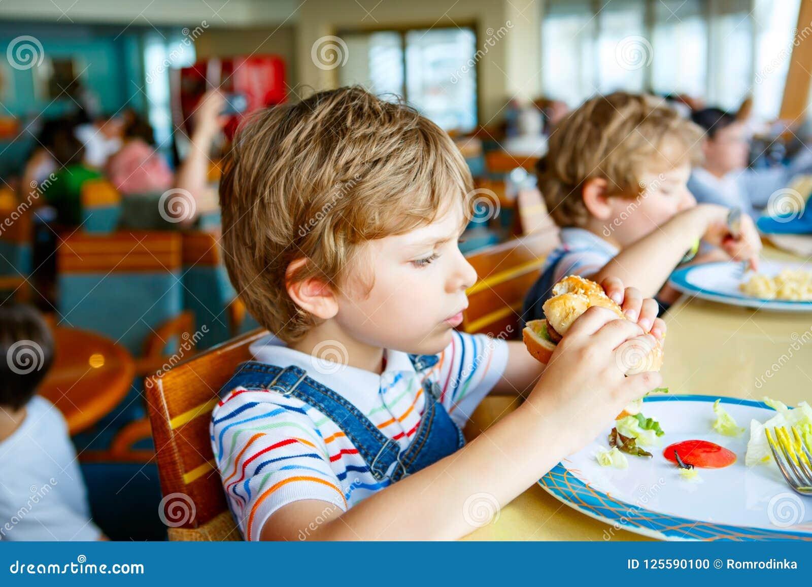 De leuke gezonde peuterjong geitjejongen eet hamburgerzitting in school of kinderdagverblijfkoffie Gelukkig kind die gezonde orga