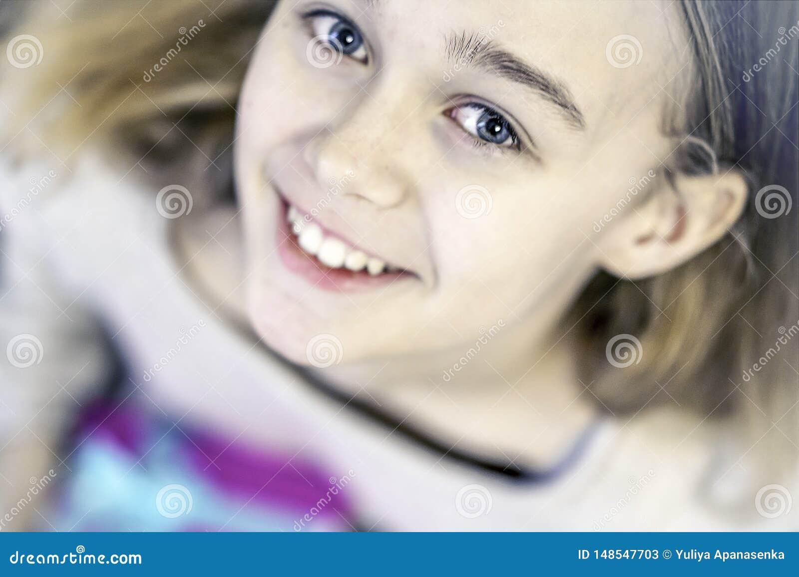 De leuke jonge meisjesholding stelt voor, glimlachend en bekijkend camera