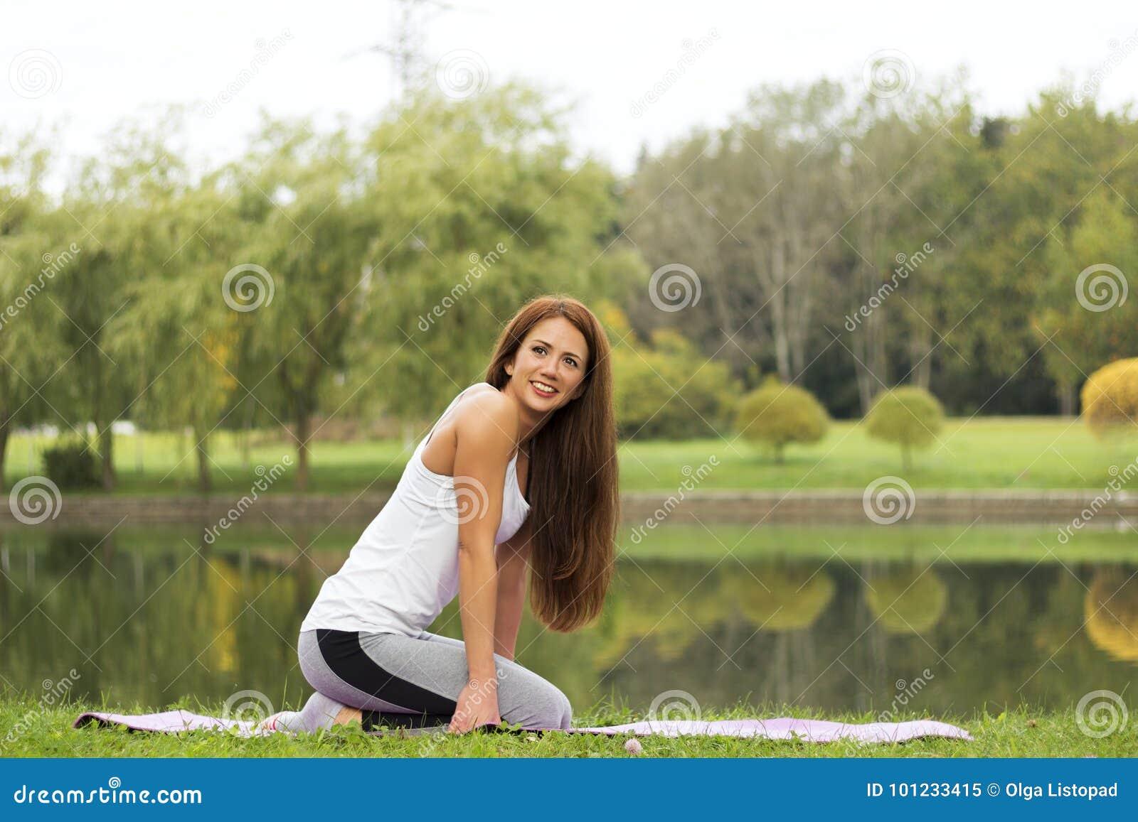 De leuke jonge mooie meisjeszitting in yoga stelt op de rivieroever heeft een rust na training gezondheid en sportconcept
