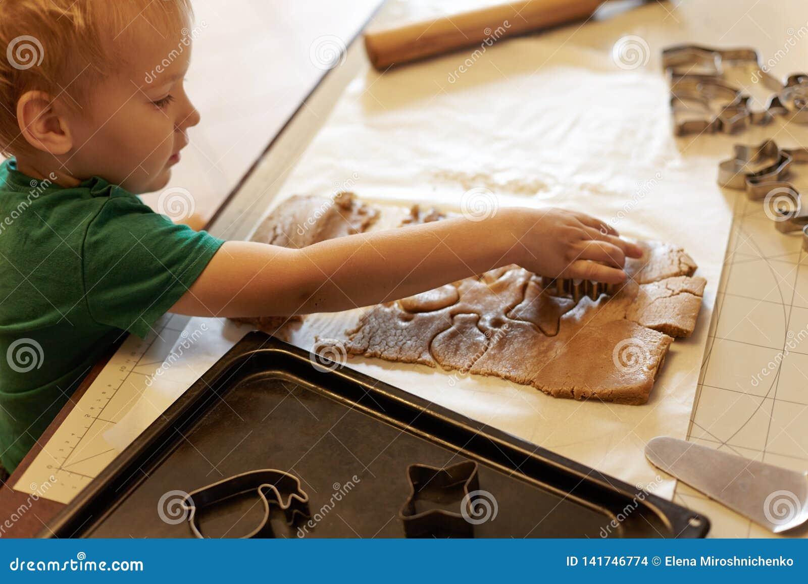 De leuke Kaukasische hulp van de babyjongen in keuken, die eigengemaakte coockies maken Toevallige levensstijl in huis binnenland
