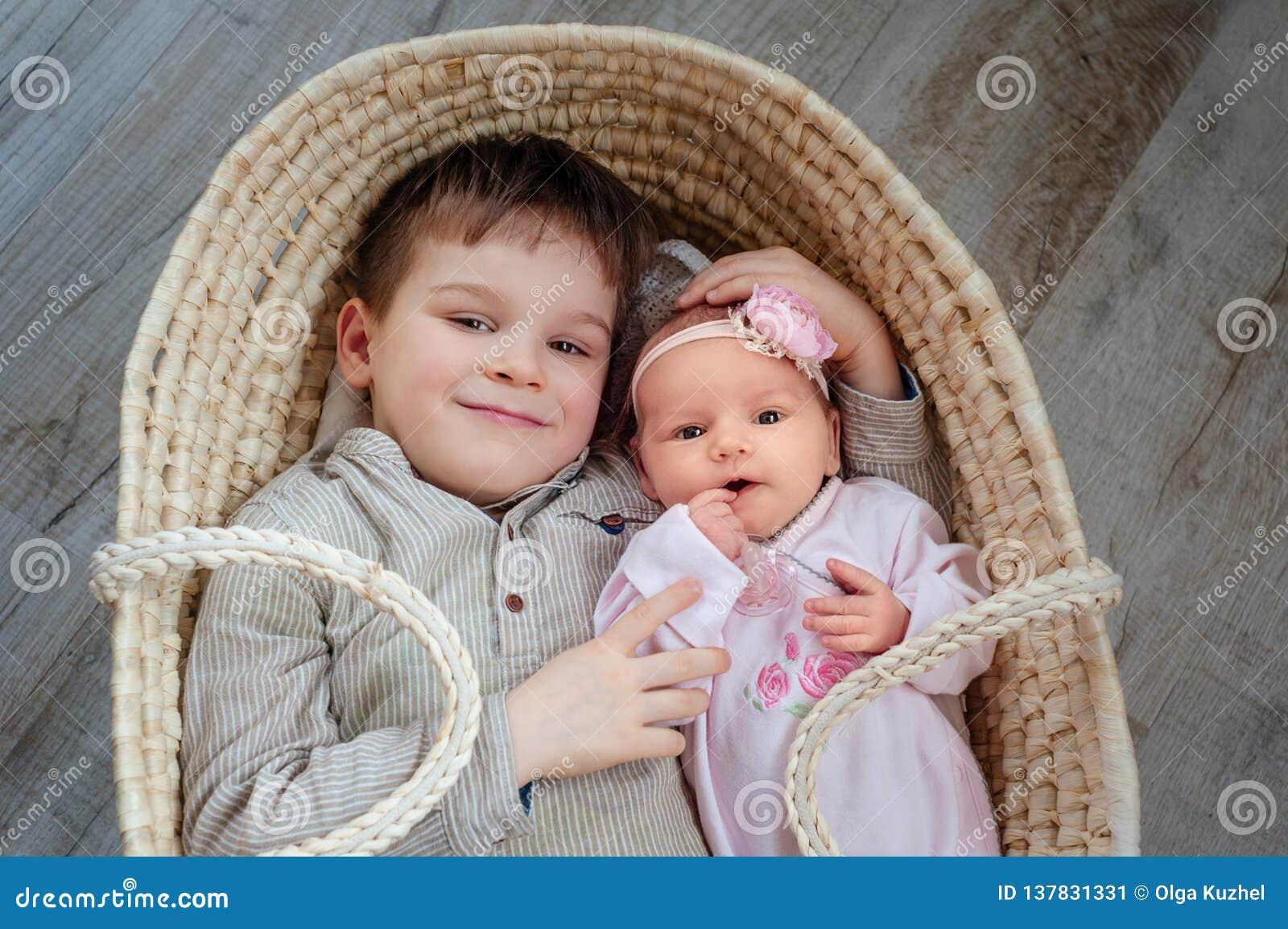 De leuke kinderen, weinig jongen 5 jaar oud, met hem pasgeboren zuster ligt in een rieten wieg