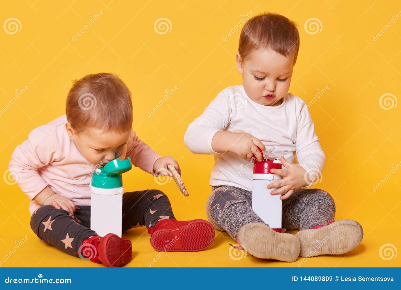 De leuke tweelingzusters hebben samen een maaltijd zonder ouders, spelen met elkaar, doorbrengen vrije tijd Één van de zusters wi