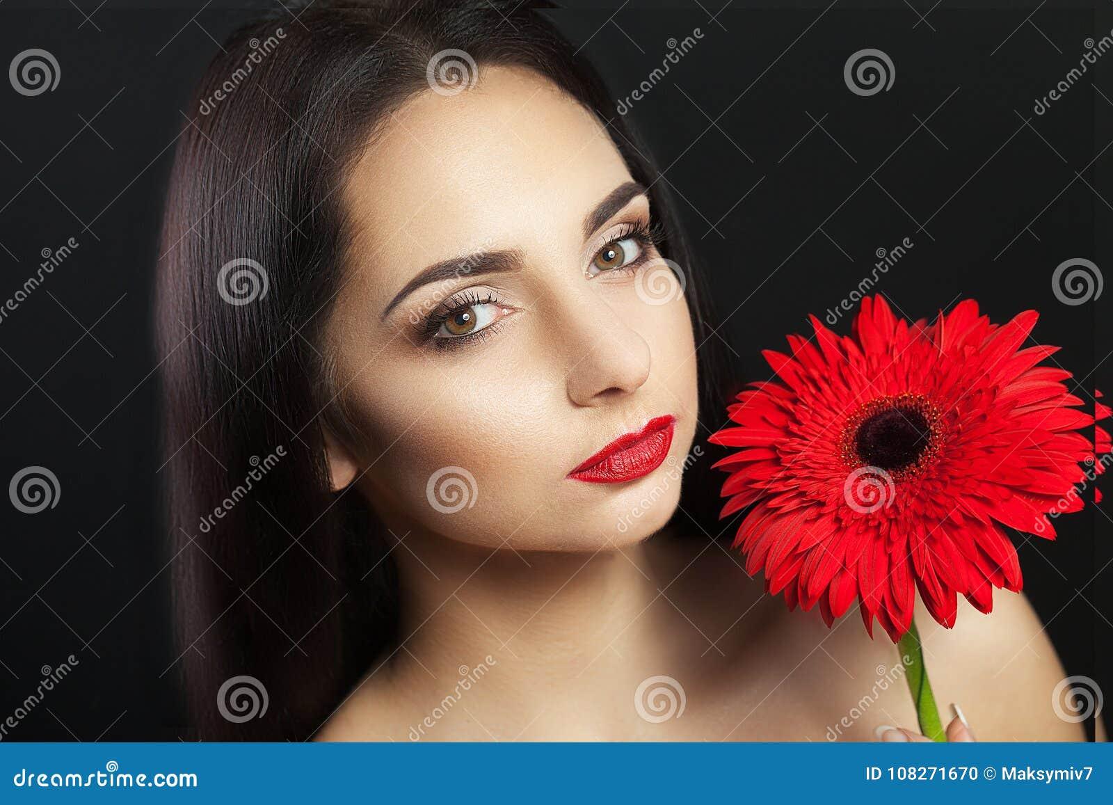 De leuke vrouw Europeanen, lichte samenstelling op haar gezicht in haar handen en haar haar roze gladiolen bloeit Vrouwelijk port