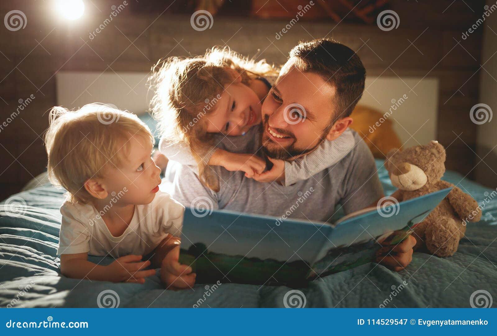 De lezing van de avondfamilie de vader leest kinderen boek vóór goin