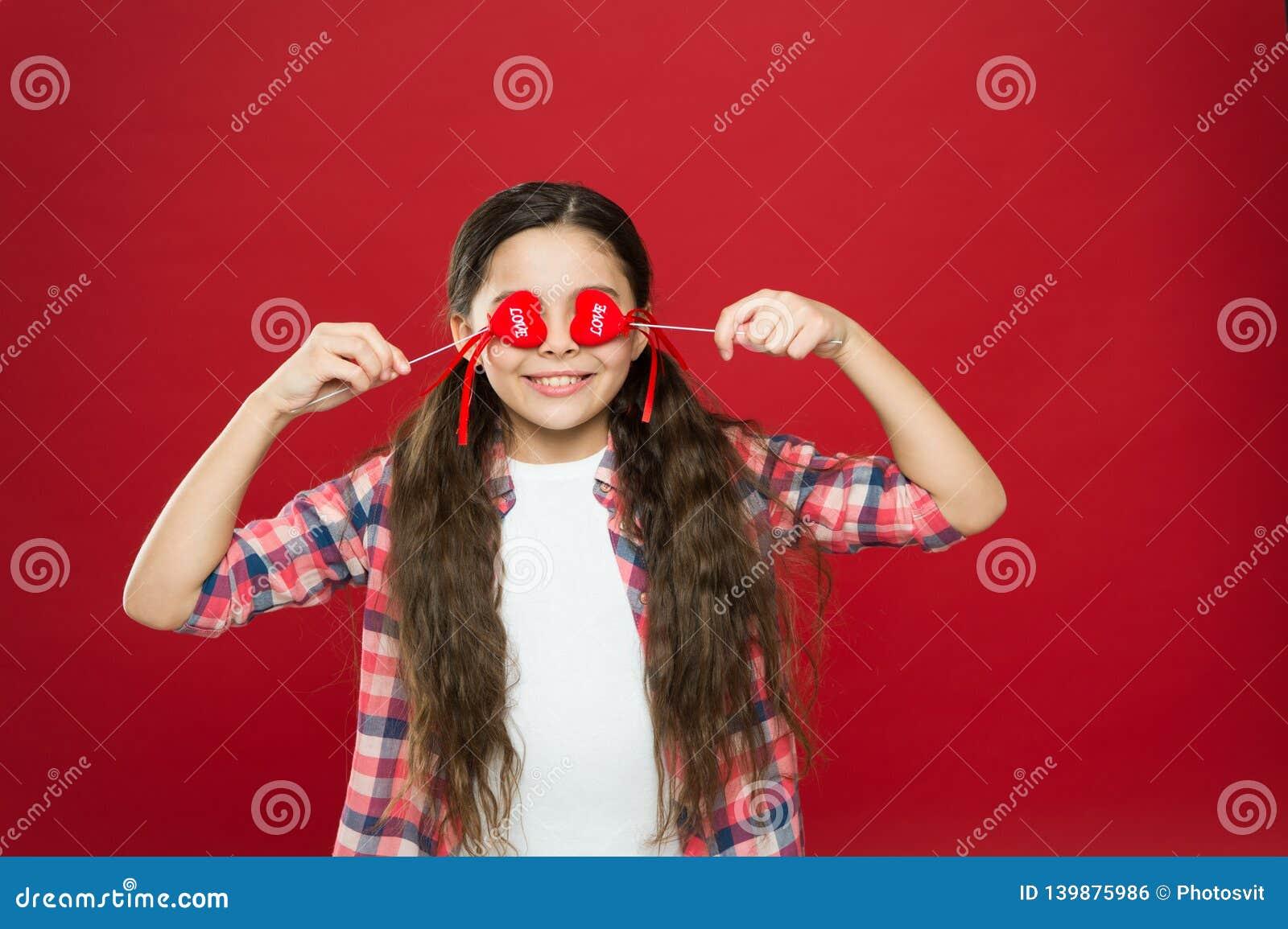 De liefde is blind Grappig meisje die ogen behandelen met harten Aanbiddelijk meisje met kleine rode harten op stokken Klein kind