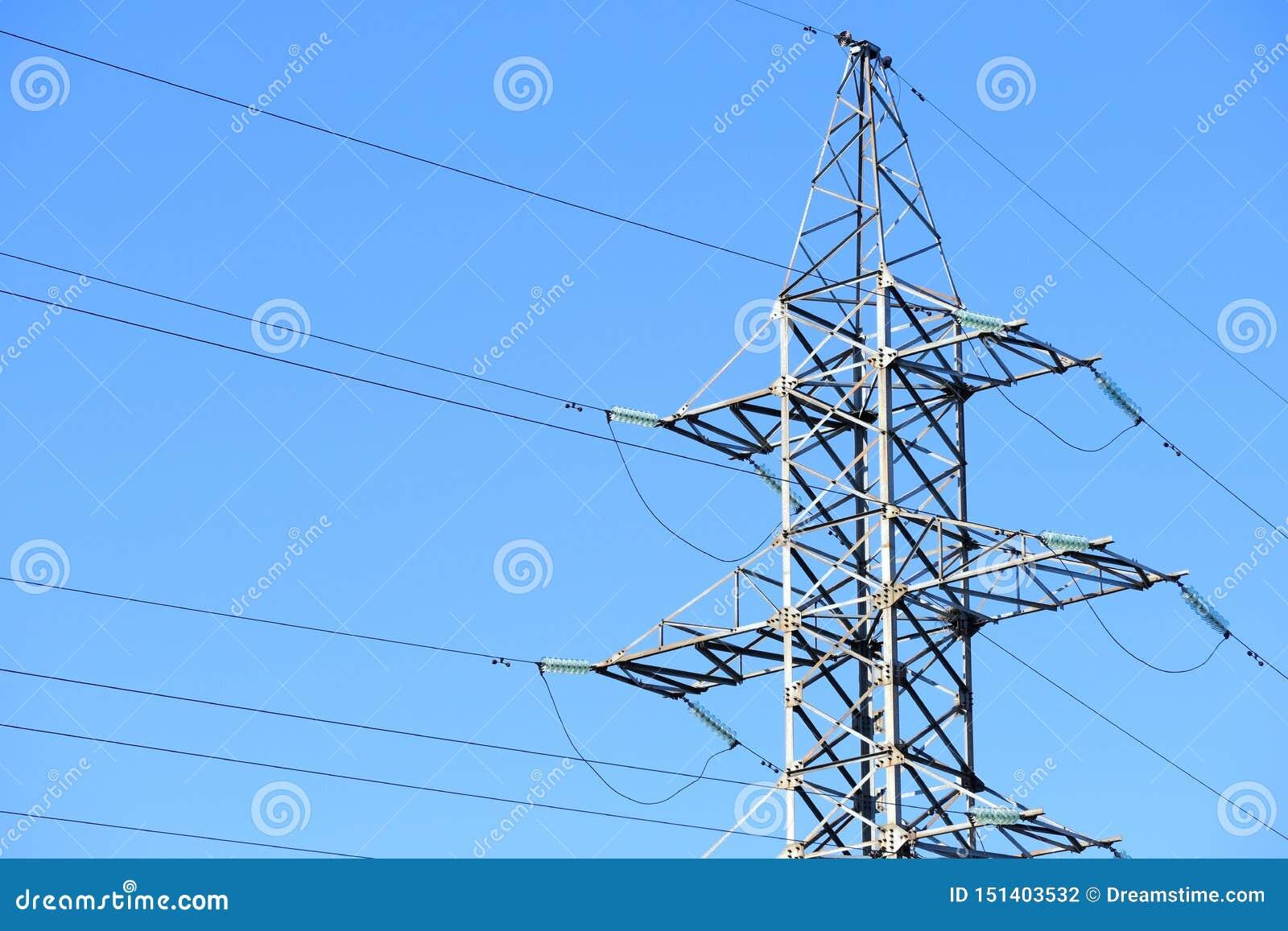 De lijn of de torenmachtslijnen van de hoogspanningsmacht tegen een blauwe hemel