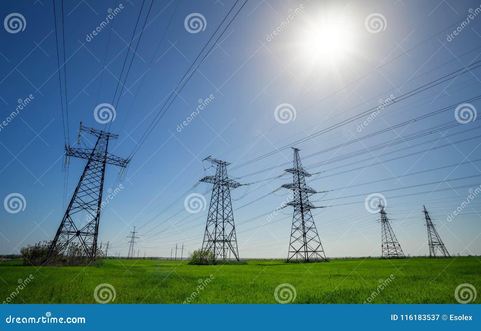 De lijnen van de hoogspanning en machtspylonen