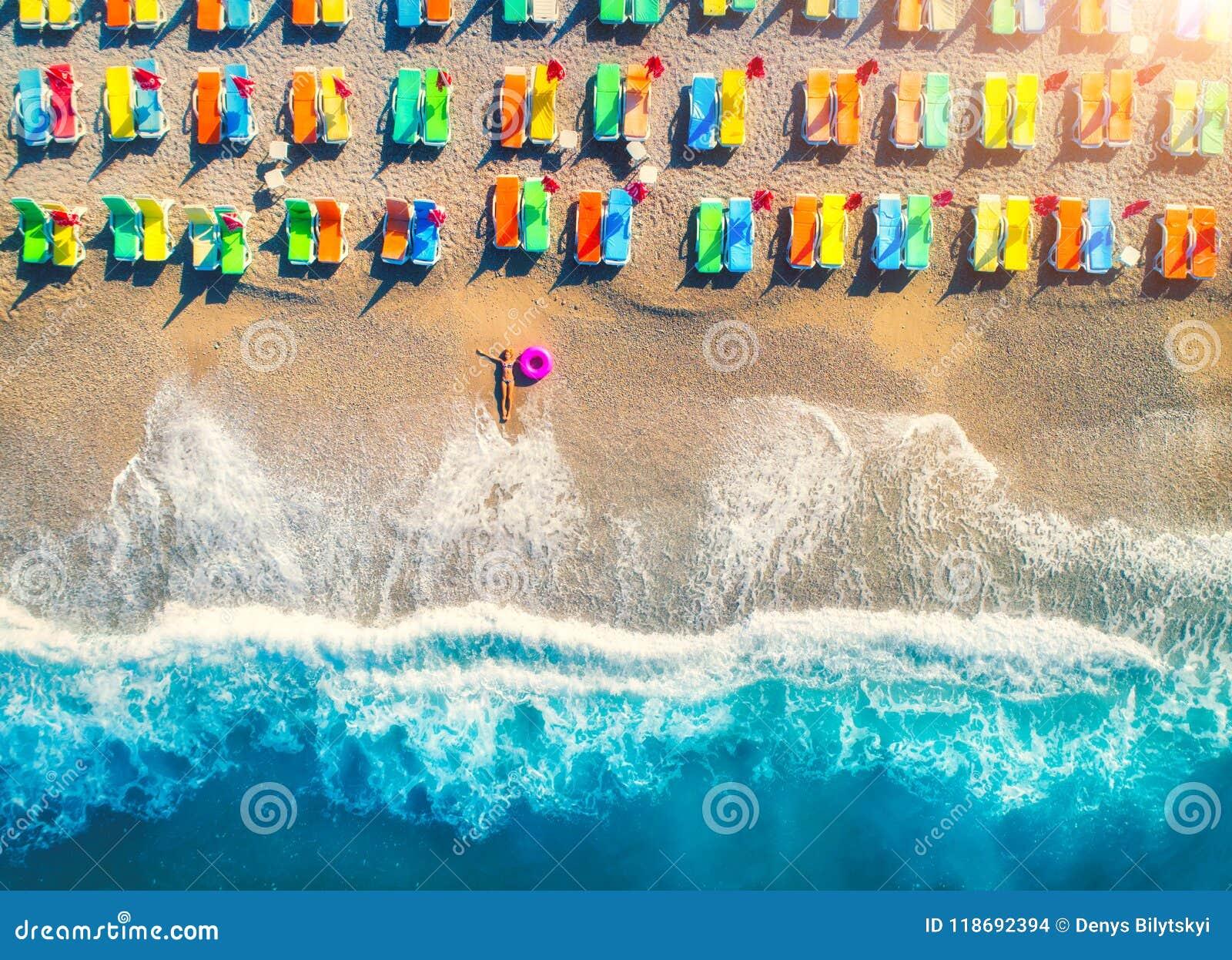De luchtmening die van vrouw met zwemt ring in het overzees liggen