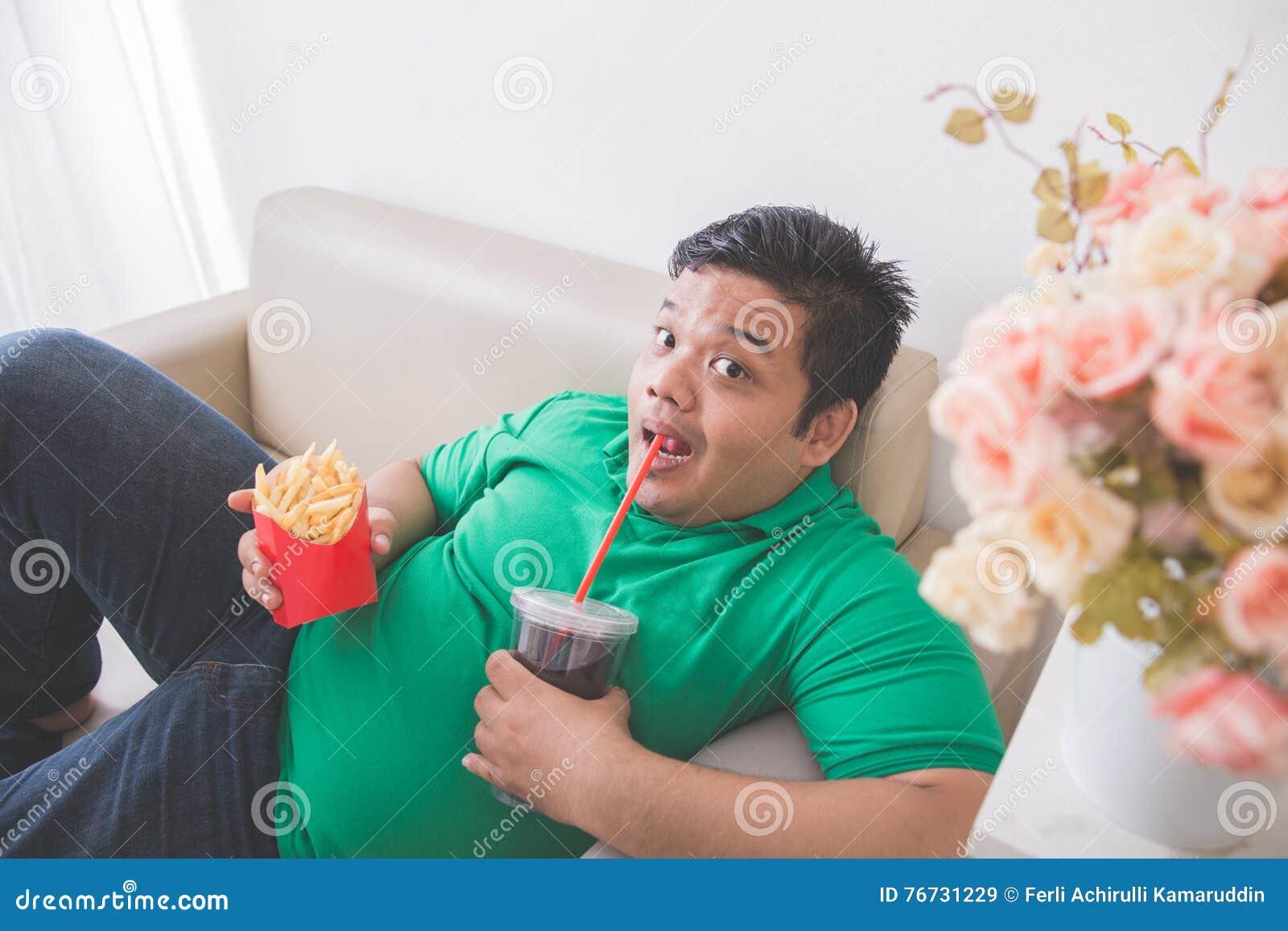 De luie zwaarlijvige persoon eet ongezonde kost terwijl het leggen op een laag