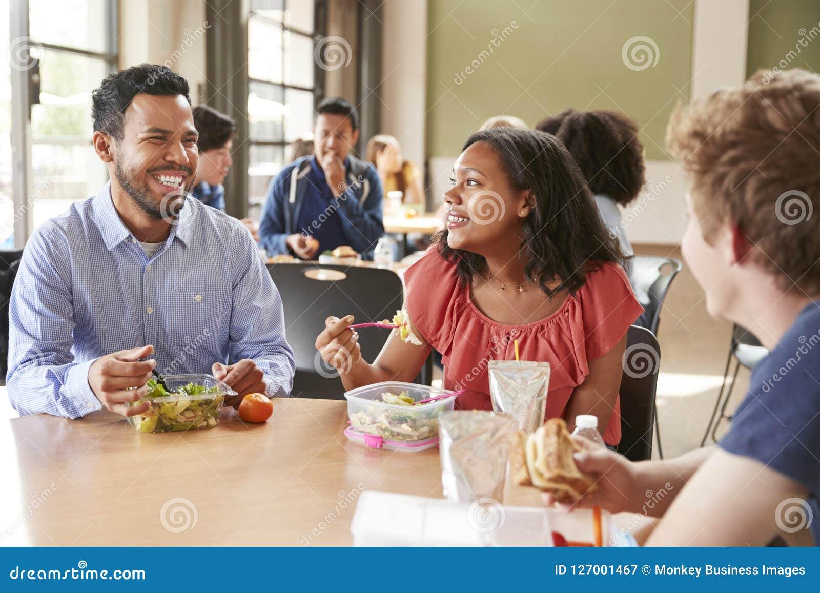 De Lunch van leraarsand students eating in Middelbare schoolcafetaria tijdens Reces