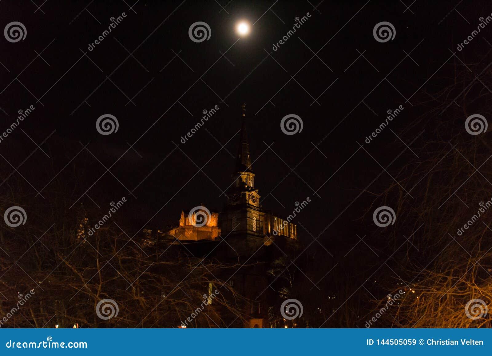 De maan over St Cuthbert en het kasteel van Edinburgh
