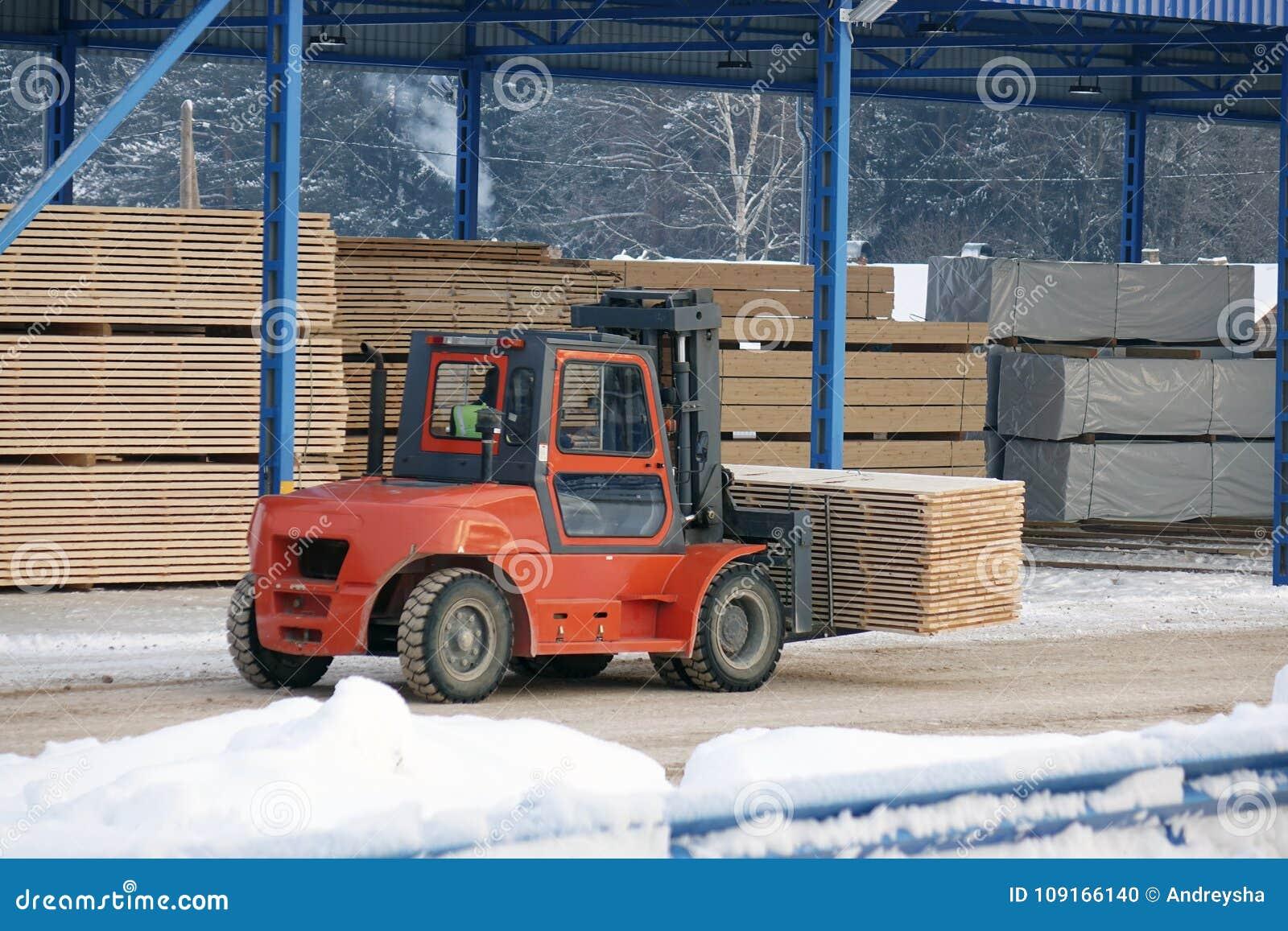De machine heft timmerhout op een houten fabriek op