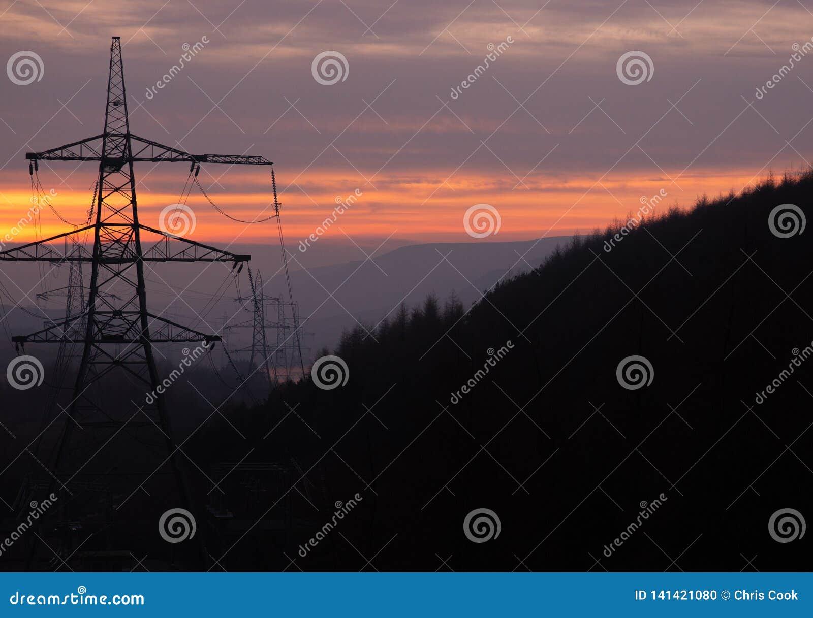De machtspylonen nemen een bos door bij Zonsondergang in het UK, Piekdistrict